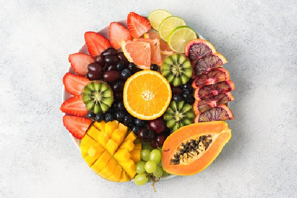 Healthy eating, assortment of raw fruits and berries platter on the off white background, top view, copy spac
