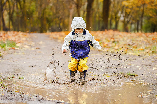 child stomping in mud puddle