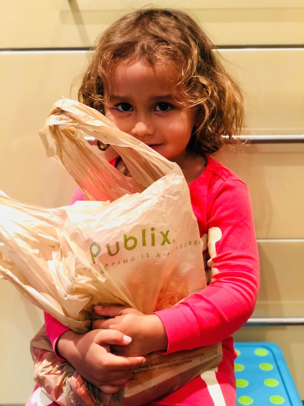 toddler with a Publix bag