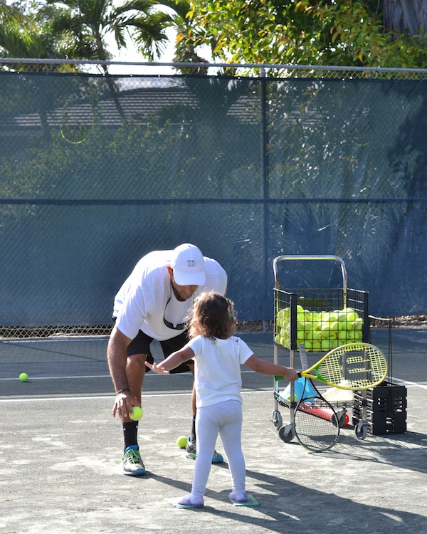 toddler girl learning to play tennis