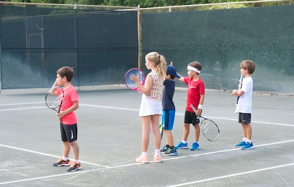 group of kids playing tennis