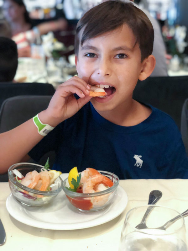 boy eating shrimp during cruise vacation
