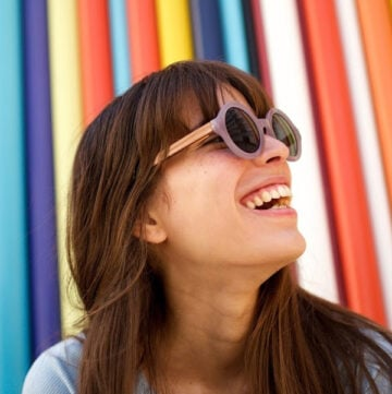 Close up portrait of cheerful young woman laughing with sunglasses against colourful background