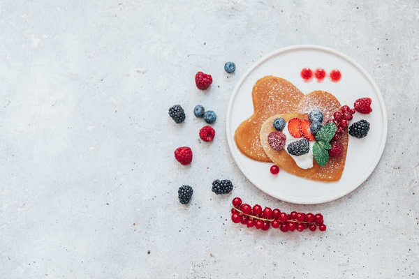 Homemade heart shaped pancakes with berries. Breakfast or brunch for Valentine's Day.