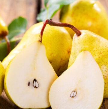 fresh ripe pears with leaves on wooden table