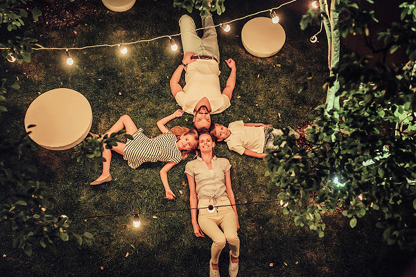 Top view of happy family is spending time together in park in the evening with garland of light bulbs. Parents with children are having fun and enjoying being together. Mom, dad, son and daughter outdoors.