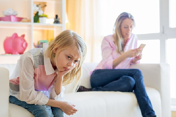 Mom on phone while child sits sadly by